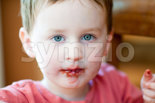 Little boy eating chocolate covered strawberries Stock Photo