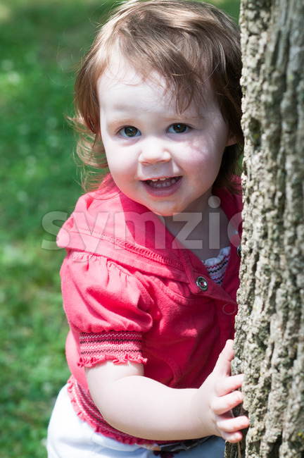 View of Young girl outside at park hugging standing next to tree