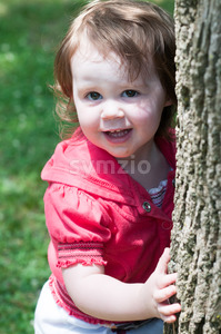 Young girl outside at park hugging standing next to tree Stock Photo