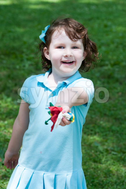 Young girl outside at park holding balloons Stock Photo