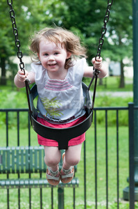Young girl having fun outside at park on a playground swing set Stock Photo