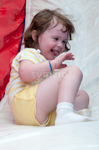 Young happy girl child riding inflatable slide outdoors on a warm summer day. Stock Photo