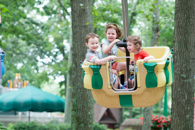Young siblings, 1 boy and 2 girls, having fun on boardwalk amusement ride Stock Photo
