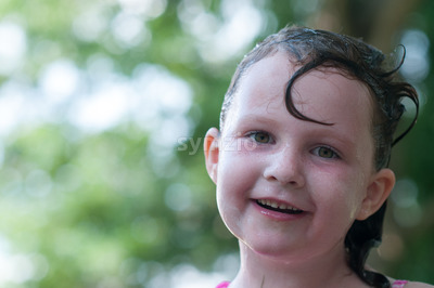 Little girl outside with wet hair after swimming Stock Photo
