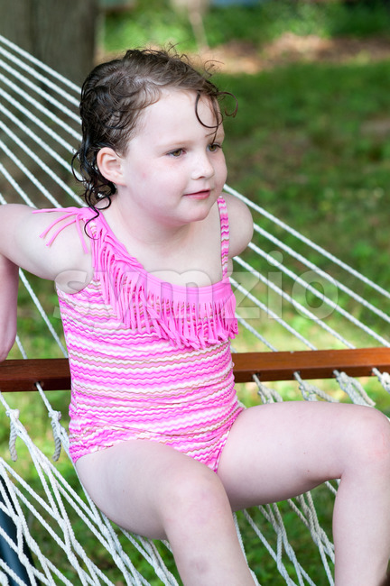 View of Young girl outside in swimming suit sitting on hammock