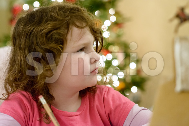 View of Cute little child girl writes the letter to Santa Claus near Christmas tree indoors.
