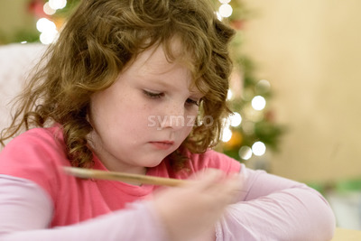 Cute little child girl writes the letter to Santa Claus near Christmas tree indoors. Stock Photo