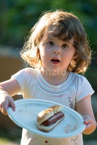 Cute toddler girl eating hot dog hotdog Stock Photo