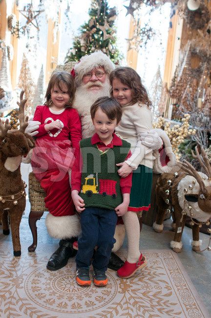 3 Siblings, 2 girls and 1 boy sitting on Santa with decorated tree in background Stock Photo