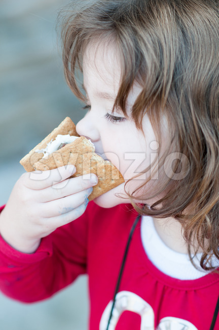 Young little girl is eating a s'more made from graham crackers, roasted marshmallows and chocolate. Her mouth is messy and she is taking a toothy bite Stock Photo