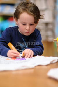 Young boy sitting down at desk indoors coloring with markers Stock Photo