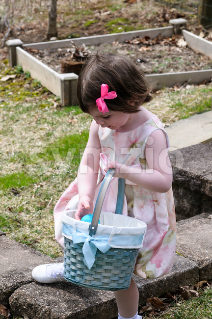 Young Girl Outside Dressed Up for Easter holding Basket Stock Photo