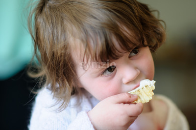 Portrait of a cute little girl inside eating potato chip with sour cream dip on it Stock Photo