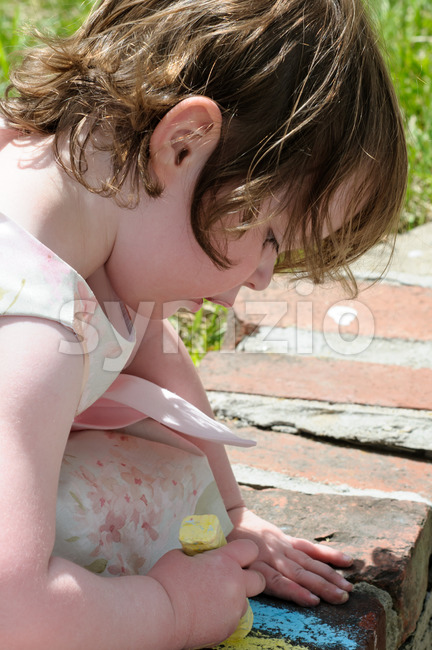 Portrait of a cute little girl outside writing on bricks with sidewalk chalk Stock Photo