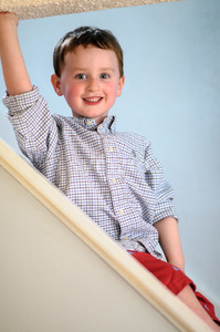 Portrait of a cute little boy inside on stairs Stock Photo
