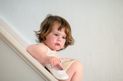 Portrait of a cute little girl inside on stairs holding dress show Stock Photo