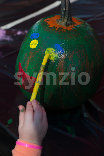 View of Happy little kid at harvest festival, painting a face of colors green, yellow and red on a pumpkin.