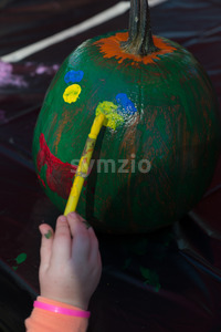 Happy little kid at harvest festival, painting a face of colors green, yellow and red on a pumpkin. Stock Photo