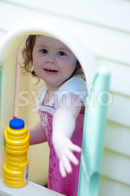 Young little girl playing in toy house in backyard on a sunny day Stock Photo