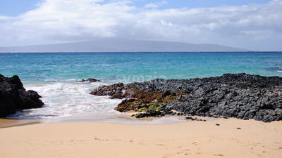 Private beach with sand and lava rocks in Maui Hawaii Stock Photo