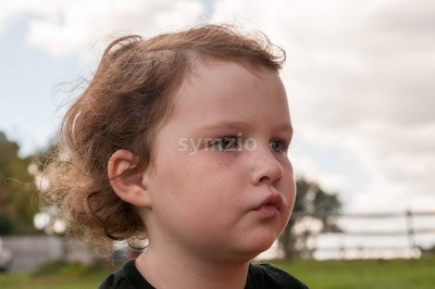 Young girl outside looking over at pumpkin fields Stock Photo