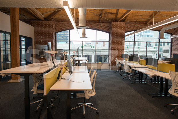 View of trendy modern open concept loft office space with big windows, natural light and a layout to encourage collaboration, ...