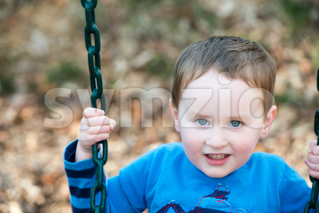 Young boy having fun outside at park on a playground swing set Stock Photo