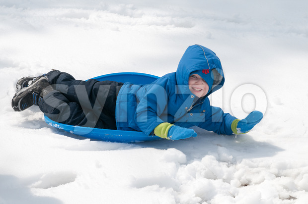 View of young little boy enjoying sledding outside on a snow day
