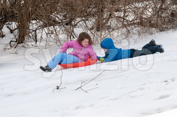 Young little girl enjoying sledding outside on a snow day while her brother holds onto the back dragging along after her Stock Photo