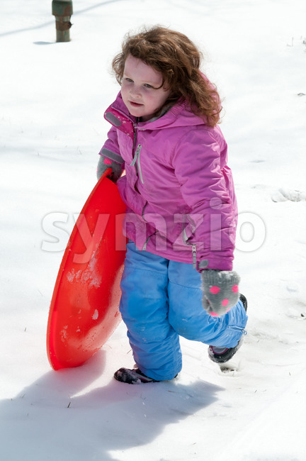 View of Young little girl enjoying sledding outside on a snow day
