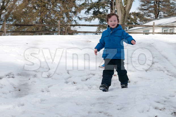 Young little boy enjoying sledding outside on a snow day Stock Photo