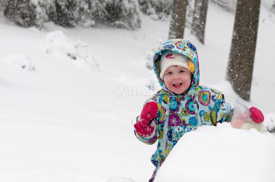 Happy toddler girl in warm coat and knitted hat tossing up snow and having a fun in the winter outside, outdoor portrait Stock Photo
