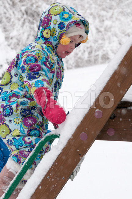 View of happy toddler girl in warm coat and knitted hat tossing up snow and having a fun in the ...