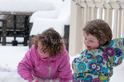 Happy toddler sibling girls in warm coat and knitted hat tossing up snow and having a fun in the winter outside, outdoor portrait Stock Photo