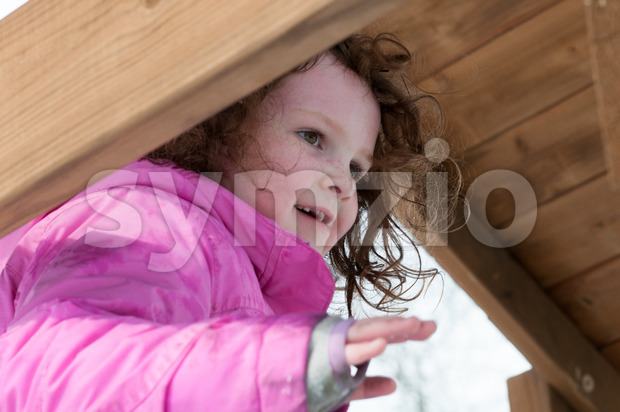 View of happy toddler girl in warm coat on on snow day and having a fun in the winter outside, ...