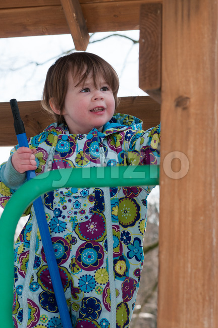 Happy toddler girl in warm coat on on snow day and having a fun in the winter outside, outdoor portrait Stock Photo