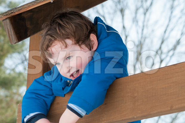 Happy toddler boy in warm coat on on snow day and having a fun in the winter outside, outdoor portrait Stock Photo