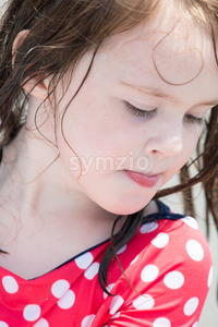 yound toddler girl having fun digging in the sand at the beach Stock Photo