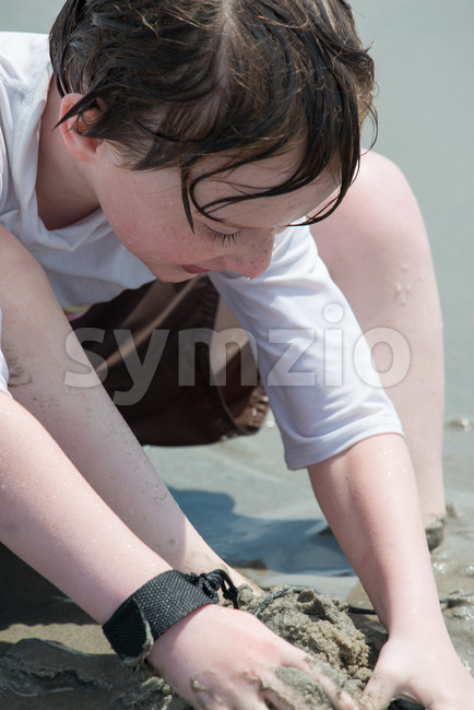 yound toddler boy having fun digging in the sand at the beach Stock Photo