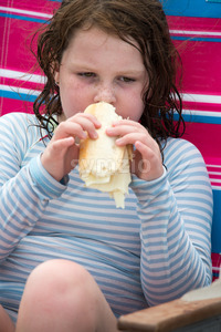 Child girl with cheese hoagie sandwhich on a deck chair by the ocean Stock Photo