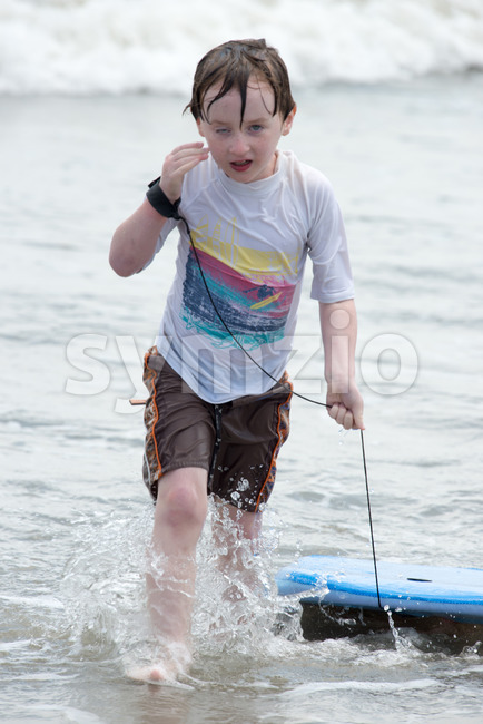 Boy coming out of the ocean waves with a boogy board Stock Photo