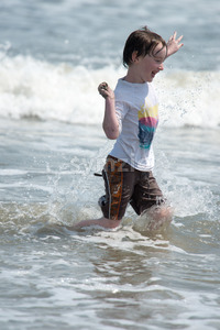A happy young boy child running playing and having fun in the surf and waves of a sandy sunny beach Stock Photo
