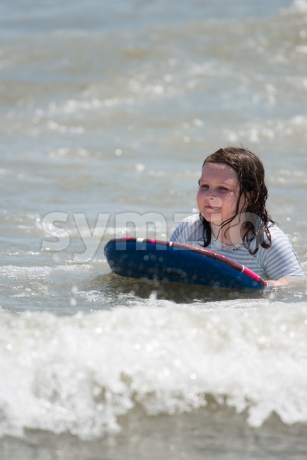 Girl surfing the waves in the ocean on a boogy board Stock Photo