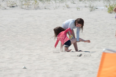 Sibling girls playing in the sand on summer beach Stock Photo