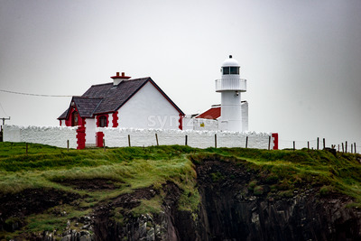 The lighthouse on a cliff in Dingle, Ireland Stock Photo