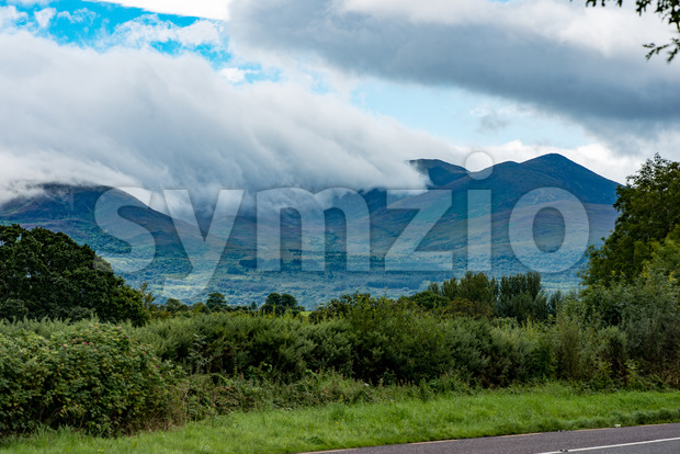 Mountains, Fields and Lake on Cloudy Day in Killarney Ireland Stock Photo