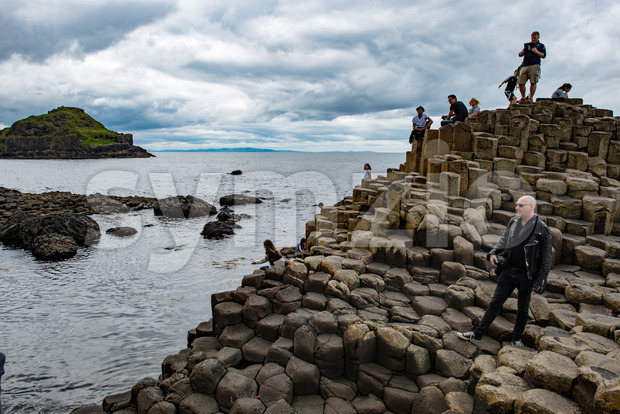 COUNTY ANTRIM, NORTHERN IRELAND - AUGUST 27, 2017: Group of tourists exploring the Giant's Causeway Stock Photo
