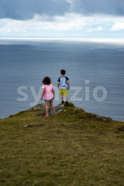 View of Girl and Boy looking out over Slieve League Cliffs, County Donegal, Ireland