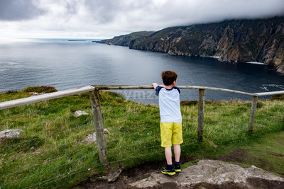 Boy looking out over Slieve League Cliffs, County Donegal, Ireland Stock Photo