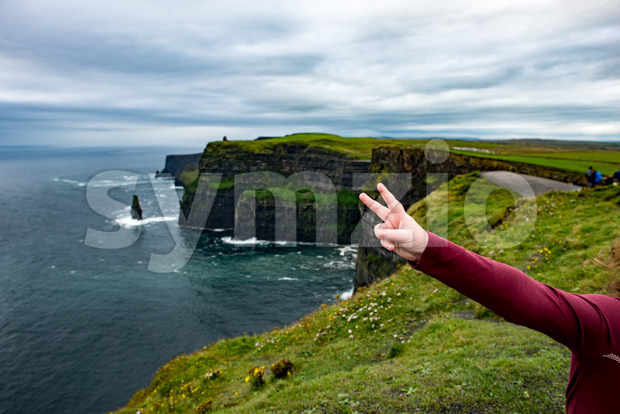 Girl at the Cliffs of Moher Tourist Attraction in Ireland Stock Photo